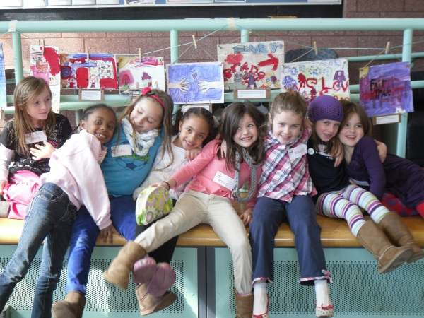 The Walden School artists sitting in front of their artwork, strung for all to see